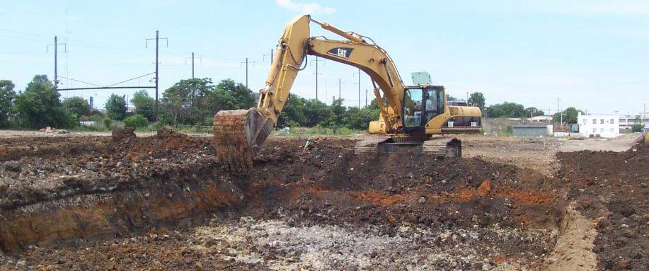 Track hoe digging out contaminated soil