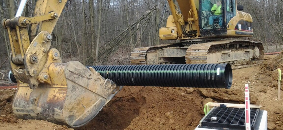Track hoe digging soil around an underground utility pipe