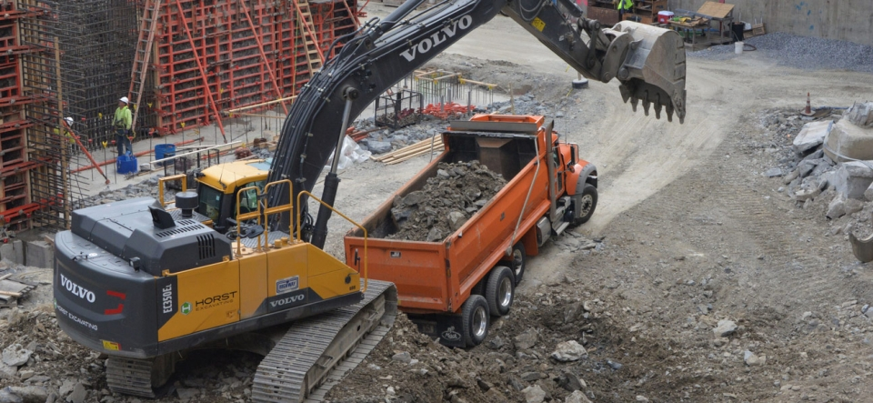 Track hoe loading dump truck on industrial excavation site